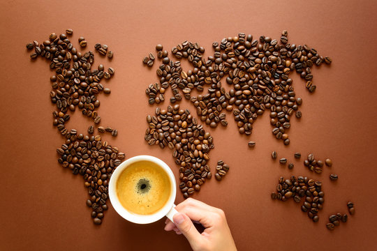 Map of the world made of roasted coffee beans on brown paper background. International coffee industry or travel planning concept