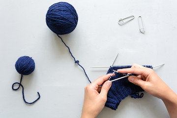 Girl knits blue hat knitting needles on gray wooden background. Process of knitting. Top view. Flat lay