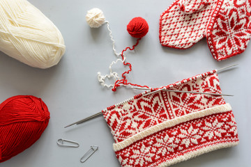 Girl knits red and white Norwegian jacquard hat knitting needles on gray wooden background. Process of knitting. Top view. Flat lay