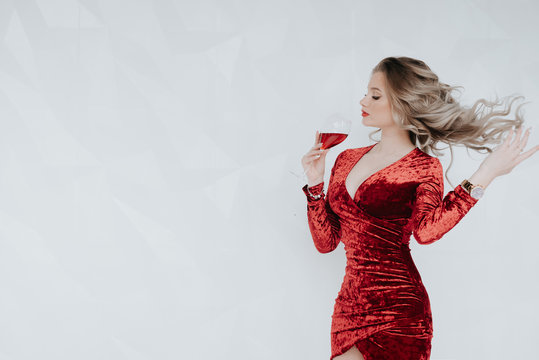 Wine. Red wine. A glass. woman drinks wine. Winemaking. Taste. Alcohol. Aperole. Woman in red. Lady in red. Business lady. A glass of wine.