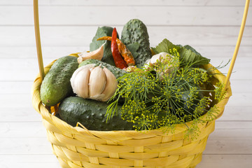 Marinated cucumbers, garlic and spices for salting in a wicker basket. Autumn harvest.