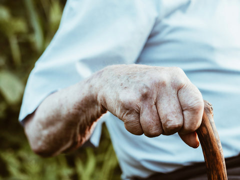 wrinkled old man' hands crossed on the stick. Close-up of a pensive grandfather sitting alone outdoors and rests on a cane.