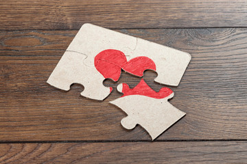 Parts of the puzzle form the heart, broken. The concept of divorce, quarrel, conflict.
