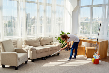 Full body portrait of young woman in white shirt and jeans cleaning carpet with vacuum cleaner in living room, copy space. Housework, cleanig and chores concept