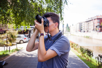 Close up view of young man with digital camera outdoors.Photographer photographing outdoor