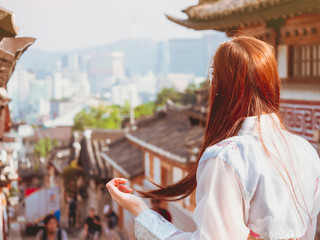 travel and tourist asia concept from backside of beauty long hair woman in korea traditional cloth (hanbok) stand, take picture and see to people in vintage town with soft focus background