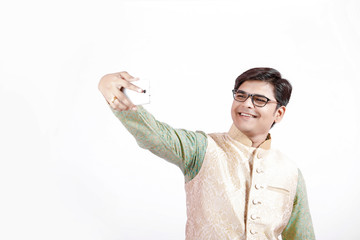 young Indian man taking selfie with mobile