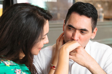 Man looks in eyes of his wife and kisses her hand