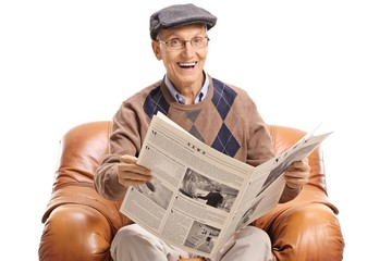 Elderly man with a newspaper sitting in a leather armchair