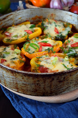 Bell peppers stuffed with vegetables and cheese with tomato sauce in a frying pan
