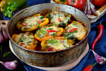 Stuffed halves of bell peppers with mince and cheese in a frying pan. European and Caucasian cuisine meal