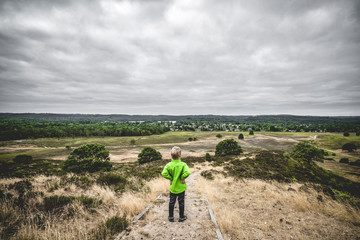 Small boy in a green jacket looking