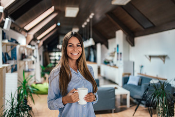 Portrait of beautiful young woman holding coffee cup at home.