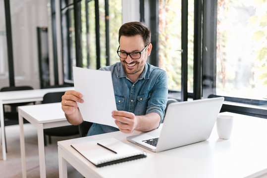 Handsome young man looking at paper documents with good results and smiling.