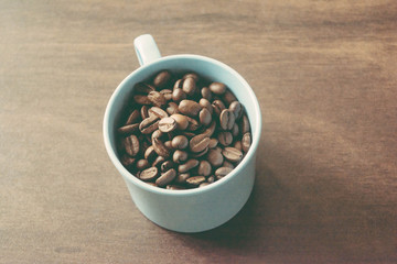 cup of coffee beans on dark wooden table