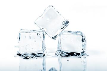Three ice cubes melting isolated on white.