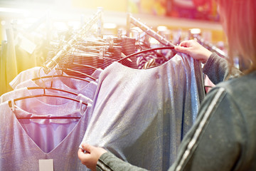 Buyer woman chooses clothes in store