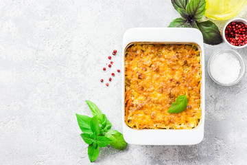 Cheesy stuffed cabbage casserole on concrete background. Top view, space for text.