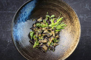 Traditional Asian eggplant ragout with scallions and sesame as top view in a bowl