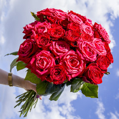 female hand holds a bouquet of red roses against the blue sky
