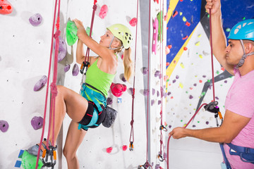 Instructor giving instructions to woman on wall climbing