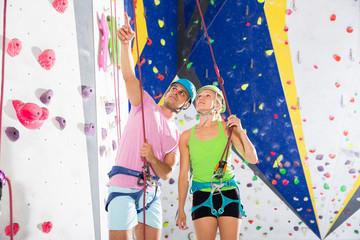 Man instructing woman on wall climbing