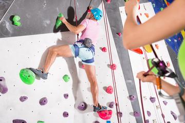 Man dressed in rock climbing at bouldering gym