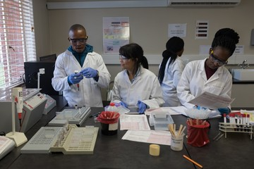 Laboratory technicians interacting with each other