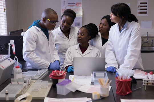 Group of laboratory technicians discussing over laptop