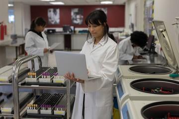 Laboratory technician using laptop