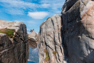 Portrait of a extreme plan travel for the handsome old man on the stone of the kjerag in the mountains kjeragbolten of Norway,   selfie on a smartphone holding in your freedom hand