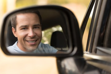 Portrait of a Smiling Man Driving a Car in Side View Mirror
