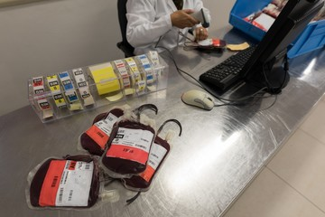 Laboratory technician scanning bar code of blood bags