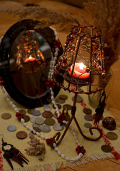 A burning candle in a decorative candlestick is reflected in a mirror on the background of coins, beads and earrings