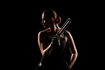 Military woman with a gun over black background