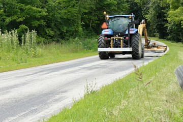 tractor mowing along a roadside in a rural setting