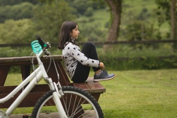 Side view of girl sitting on bench at park