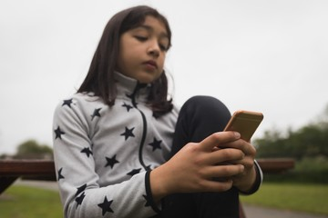 Girl using mobile phone at garden
