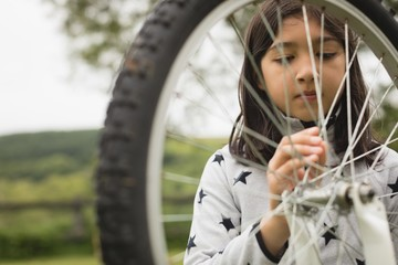 Girl repairing bicycle