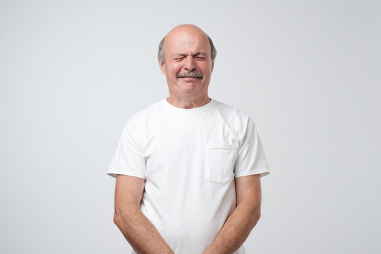 Unhappy senior man like weeper crying standing over gray background. He is offended and upset.