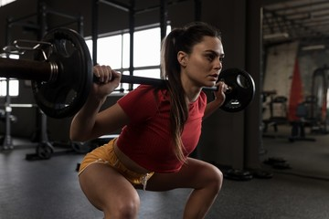 Woman doing a barbell squat in fitness studio