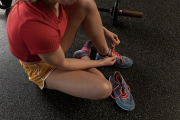 Woman tying shoe laces in fitness studio