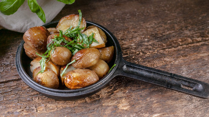 Baked potatoes in a frying pan with basil. Wooden background. Close-Up