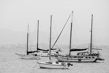 Barcos de Mastro em um dia nublado e cidade ao fundo