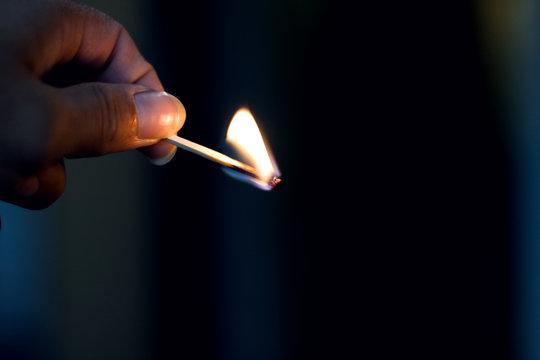 Burning match in hand in the dark