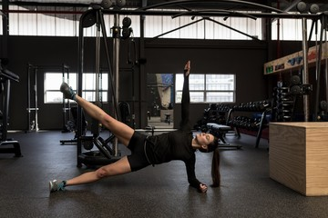 Woman doing side plank exercise in fitness studio