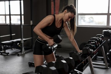 Women exercising with dumbbell in fitness studio