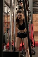 Woman exercising on machine at fitness studio