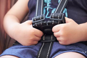 safety belt in the baby stroller, a small child tries to undo lock