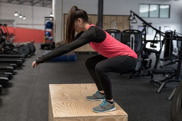 Woman doing squat exercise in fitness studio